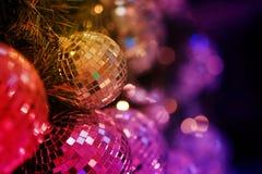 关闭镜子球或圣诞节球对装饰圣诞节节日的有bokeh五颜六色的背景 免版税库存照片