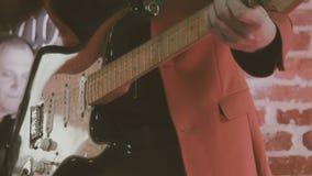 关闭阶段的爵士乐吉他弹奏者在有斡旋人的电镀物品吉他组成凉快的即兴重复段在砖墙,葡萄酒前面 影视素材