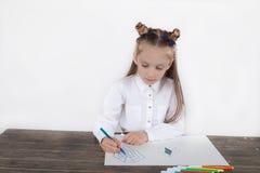 关闭集中于图画的白色女衬衫的小女孩 学龄前儿童学会如何画 幼儿园和学校 免版税库存照片