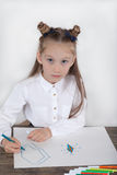 关闭集中于图画的白色女衬衫的小女孩 学龄前儿童学会如何画 幼儿园和学校 库存图片