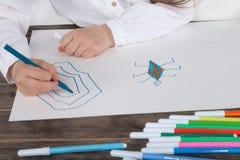 关闭集中于图画的白色女衬衫的小女孩 学龄前儿童学会如何画 幼儿园和学校 免版税库存图片