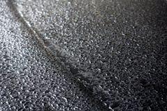 关闭雨水雨/水滴在黑表面汽车, backgr的 免版税库存照片