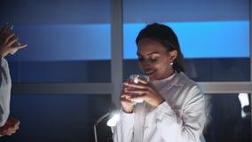 关闭非裔美国人的女性工程师谈论某事与杯子饮料在实验室