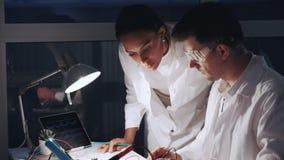 关闭非裔美国人的妇女和人防护玻璃工作的在现代电子实验室