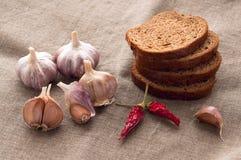 关闭面包、大蒜和胡椒静物画  库存照片