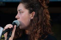 关闭面孔美丽的年轻深色的女孩,有话筒的歌唱者歌手,当唱歌活,与黑礼服时 库存照片