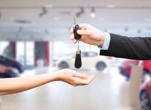 关闭顾客和推销员有汽车钥匙的 免版税库存照片