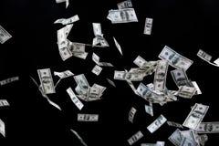 关闭飞行在黑色的美元金钱 库存图片