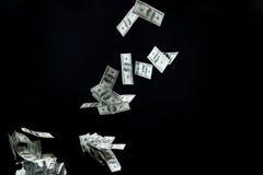 关闭飞行在黑色的美元金钱 图库摄影