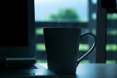 关闭饮料杯子和膝上型计算机在书桌上在家在早晨时间 免版税图库摄影