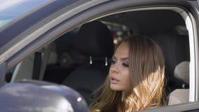 关闭驾驶汽车的一名可爱的白肤金发的妇女的射击 股票视频