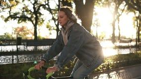 关闭骑一辆自行车在早晨公园或大道的观点的一位可爱的微笑的女性 年轻人的侧视图 股票视频