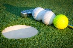 关闭高尔夫球孔的图象与球的并且轻轻一击 免版税库存照片