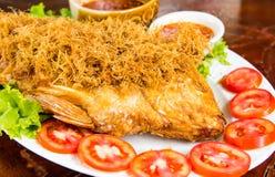 关闭鱼油煎用草本供食与新蕃茄切片和辣调味汁在白色板材在桌上 库存图片