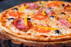 关闭鲜美西西里人的薄饼用烟肉、橄榄和蕃茄 免版税库存照片