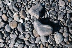 关闭黑被环绕的海滩石头和小卵石石头 免版税图库摄影