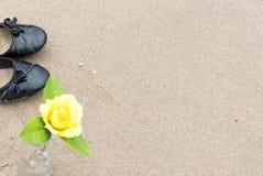 关闭黑鞋子和黄色玫瑰花到瓶  库存照片