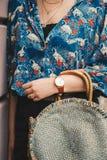 关闭,佩带夏天衬衣和一块白色和棕色模式手表的时尚博客作者,拿着一个美丽的圆的秸杆钱包 免版税图库摄影