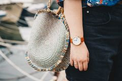 关闭,佩带夏天衬衣和一块白色和棕色模式手表的时尚博客作者,拿着一个美丽的圆的秸杆钱包 库存图片