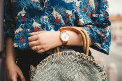 关闭,佩带夏天衬衣和一块白色和棕色模式手表的时尚博客作者,拿着一个美丽的圆的秸杆钱包 免版税库存图片