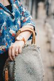 关闭,佩带夏天衬衣和一块白色和棕色模式手表的时尚博客作者,拿着一个美丽的圆的秸杆钱包 图库摄影