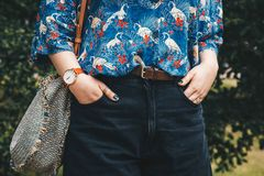 关闭,佩带夏天衬衣和一块白色和棕色模式手表的时尚博客作者,拿着一个美丽的圆的秸杆钱包 库存照片