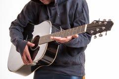 关闭,学会对弹的手一把声学吉他 库存照片