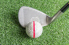 关闭,老高尔夫球和铁在人为草 库存图片