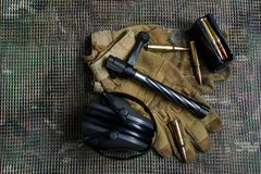 关闭,马枪夹子、弹药、手套和耳朵保护耳机谎言在背景 免版税图库摄影