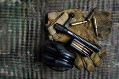 关闭,马枪夹子、弹药、手套和耳朵保护耳机谎言在背景 免版税库存图片