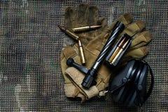 关闭,马枪夹子、弹药、手套和耳朵保护耳机谎言在multicam背景 免版税图库摄影