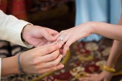 关闭,他的新娘的新郎佩带的婚戒 图库摄影