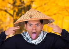 关闭戴一个亚洲圆锥形帽子的一个英俊的西班牙年轻企业人做一张傻的面孔并且去掉 库存照片