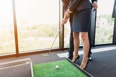 关闭 一个年长人教他的秘书打微型高尔夫球 他指挥她 库存图片