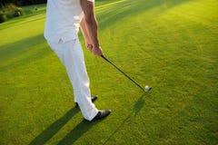 关闭 一套白色衣服的一个人准备击中与高尔夫俱乐部的球 库存照片