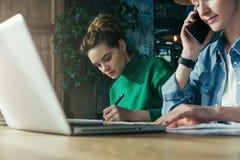 关闭 一起坐在办公室的两个年轻女商人在桌和工作上 在桌膝上型计算机和纸图 免版税库存照片