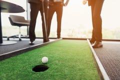 关闭 人充当微型高尔夫球的一个办公室 他们中的一个举行一家高尔夫俱乐部在他的手上 库存照片