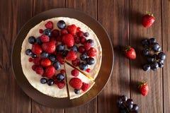 关闭 可口自创乳脂状的纽约乳酪蛋糕用在黑暗的木桌上的莓果 顶面viev 库存图片