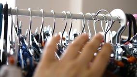 关闭 女孩在商店选择在一个挂衣架的衣裳 名牌服装,流行的服装 股票录像