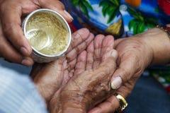 关闭给尊敬的手老家庭喝水在Songran ceremon 库存照片