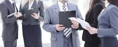 关闭 小组站立在办公室大厅的商人  免版税库存图片