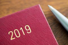 关闭2019年与笔的日志在木书桌上 库存图片