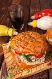 关闭 快餐 在一张木桌上的水多和开胃汉堡 木背景 免版税库存照片
