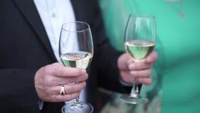 关闭黑拿着两块高玻璃用白葡萄酒的衣服和白色衬衣的白种人人 两块玻璃特写镜头  股票录像