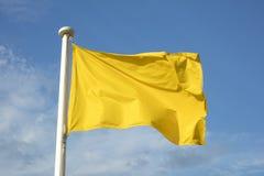 关闭黄旗在海滩,警告海况 免版税图库摄影