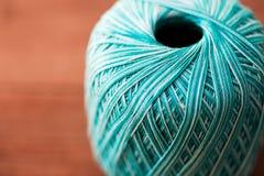 关闭绿松石在木头的编物纱球 免版税库存照片