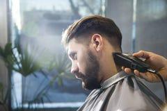 关闭整理一根严肃的businessman's头发的barber's手 免版税库存照片