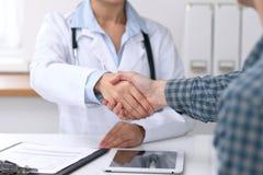 关闭医生妇女与她的男性患者握手 医学和信任概念 免版税图库摄影