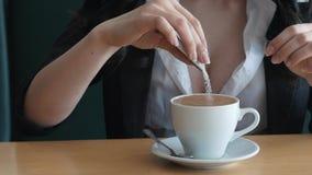 关闭年轻白种人妇女倾吐的糖英尺长度入一个杯子浓咖啡咖啡 股票录像
