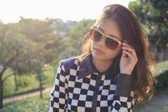 关闭年轻美丽的亚裔妇女佩带的太阳glasse的面孔 图库摄影